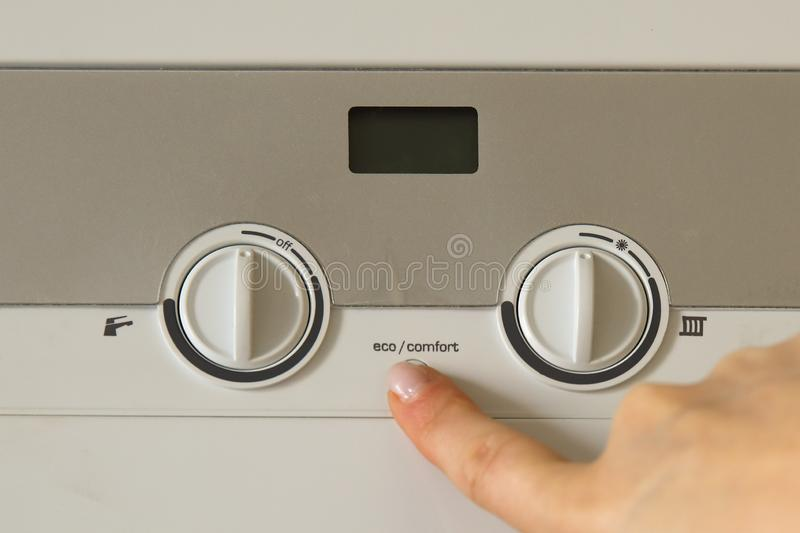 Woman hand push an installation button of home gas heating boiler royalty free stock photography