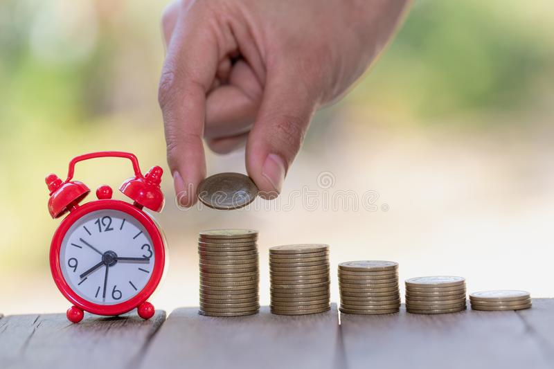 Woman hand put coins to stack of coins, a saving money for future investment concept stock photography