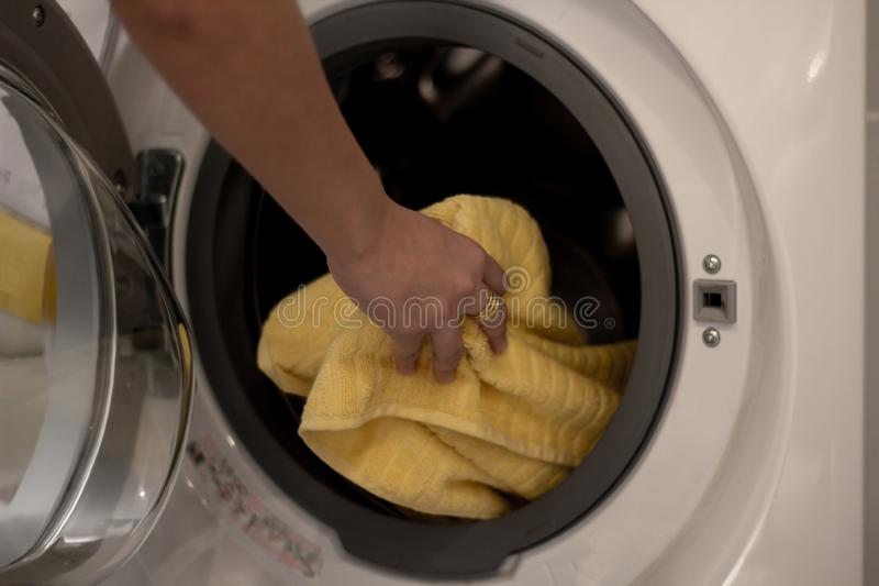 Woman hand put yellow towel into washing machine. Housewife work laundry at home stock photos
