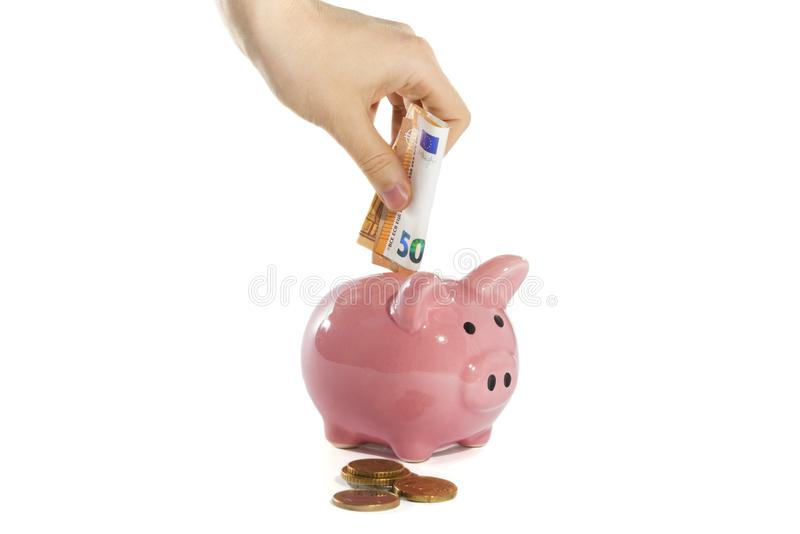 Woman hand puts money into the piggy bank royalty free stock photo
