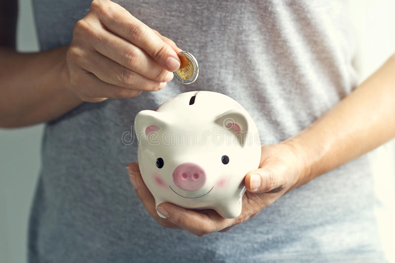 Woman hand putting coin into piggy bank royalty free stock images