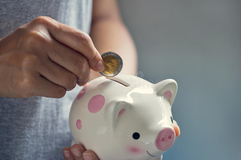 Woman hand putting coin into piggy bank stock image