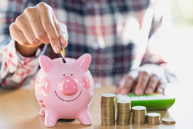 Woman hand putting coin into piggy bank. Saving money wealth and stock image