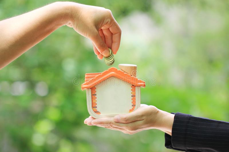 Woman hand putting a coin into wooden house on natural green background, Saving money and real estate concept royalty free stock photos