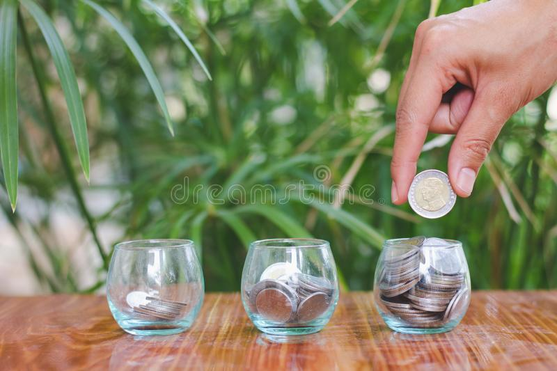 Woman hand putting coinIn the glass jar. Saving money wealth and financial concept royalty free stock photo