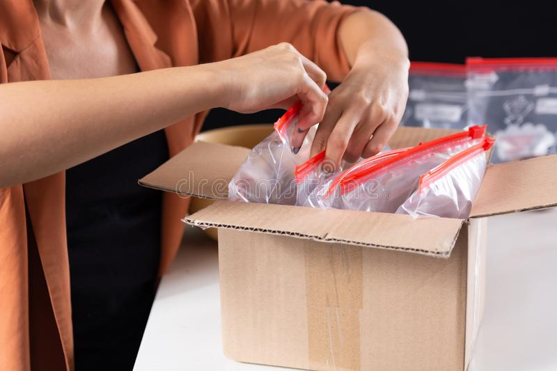 Woman hand putting zip bags in package or sending box. Preparing a shipment to send to the customer. Trade and mail concept. Close up, selective focus royalty free stock image