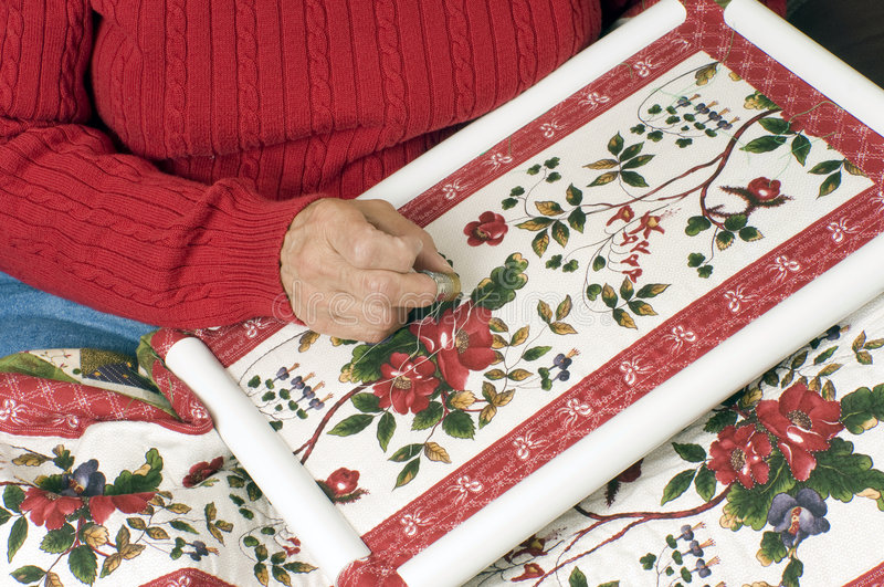 A woman hand quilting. A cotton quilt using a plastic frame stock image