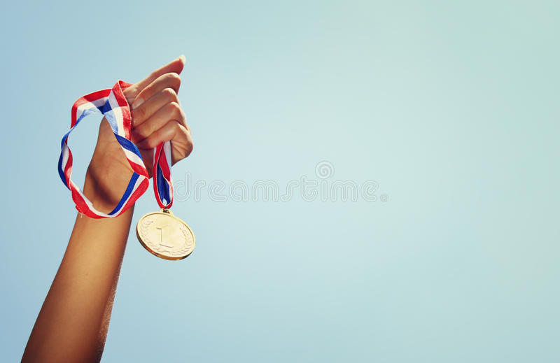 Woman hand raised, holding gold medal against sky. award and victory concept royalty free stock image