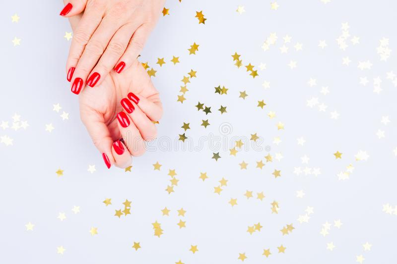 Woman hand with red manicure on blue background with sprinkles. stock photography