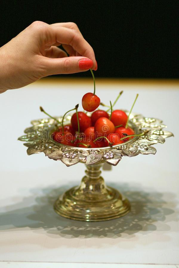 Female hand picking up cherry from antique silver bowl royalty free stock photos