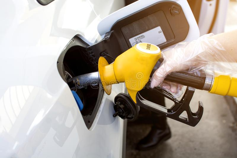 Woman hand refilling and pumping gasoline oil the car with fuel at he refuel station in Europe royalty free stock photos