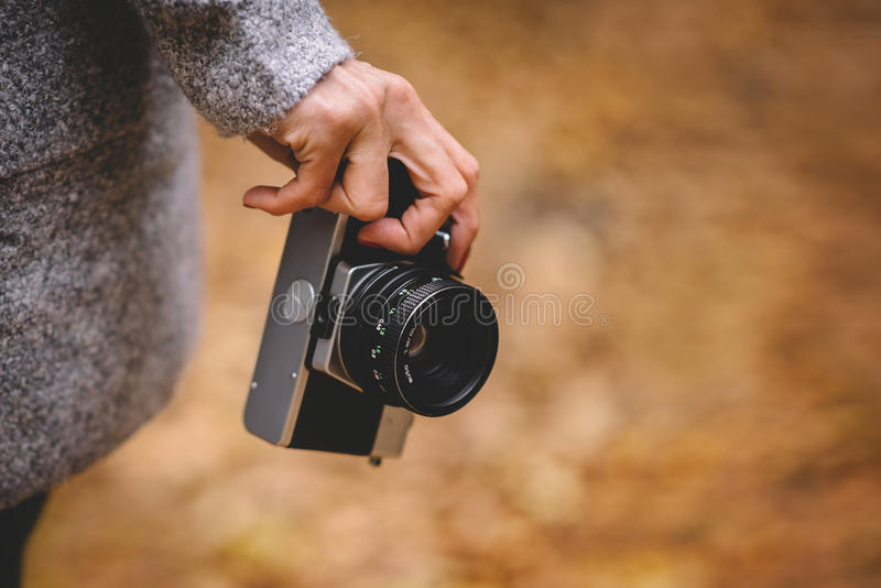 Woman hand with retro analog film camera. Concept for travel, wanderlust, outdoor adventure. Natural fall, defocused. Bokeh background. Shallow depth of field stock photo