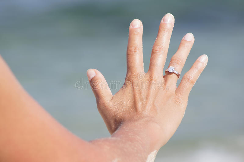 Woman hand with ring on the beach stock photography