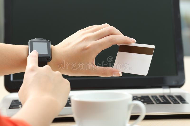 Woman hand shopping online with smart watch. Woman hand shopping on line with a smart watch and a credit card with a laptop in the background stock images