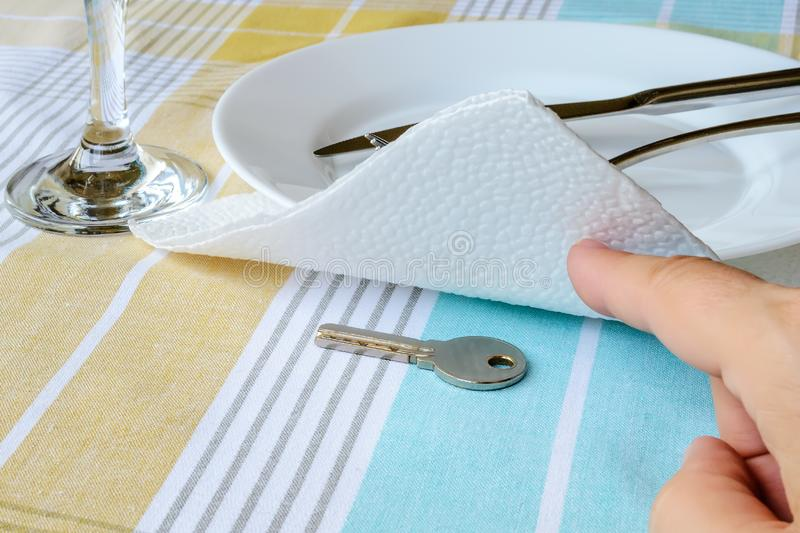 Woman hand shows the key under the paper napkin near white plate on the dining table. To hide, to find or to forget a key in a stock images