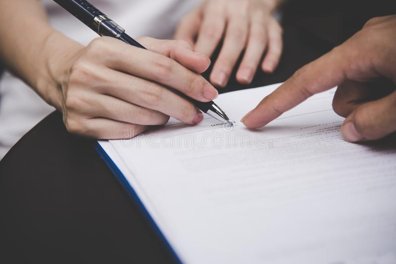 Woman hand signing a contract for building house with architect man. stock photos