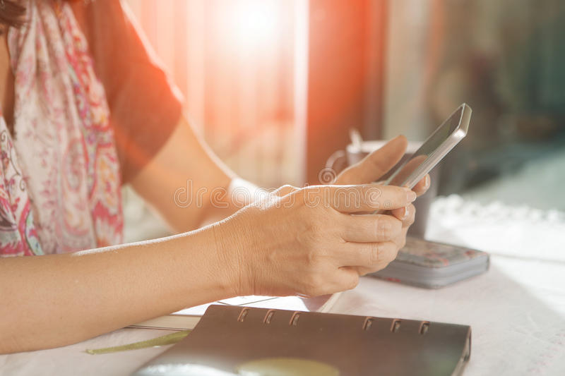 Woman hand sitting on working table and using smartphone ,for pe royalty free stock photos