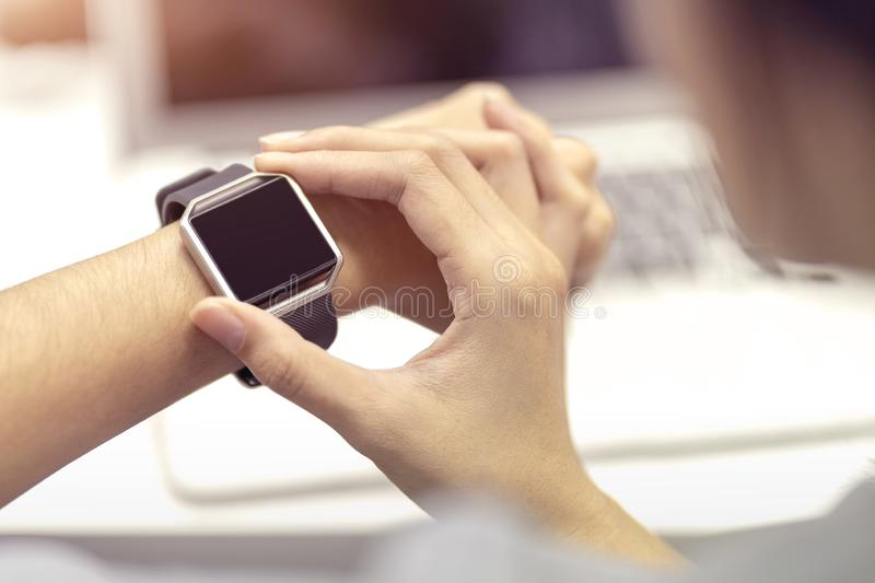 Woman hand with smart watch on wrist, wearable watch and technology computer laptop for communication, checking time stock photography