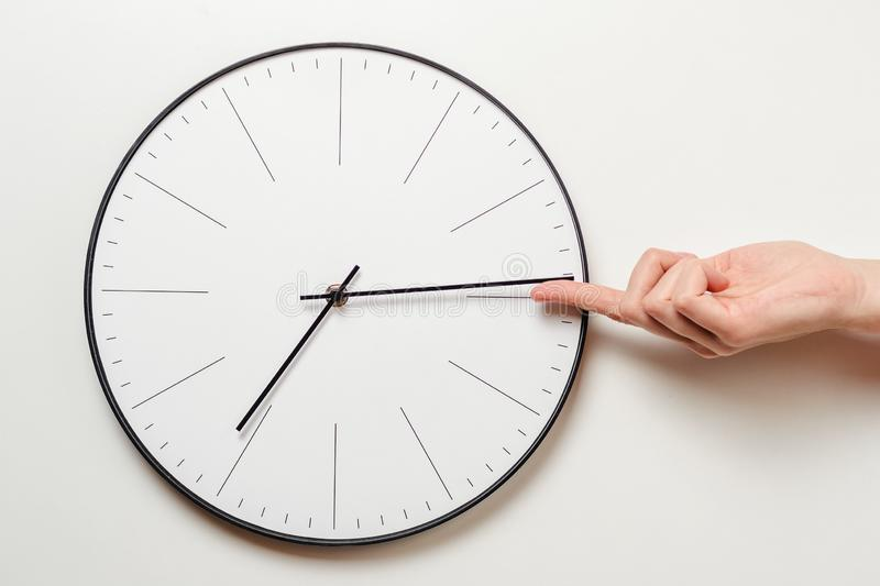 Woman hand stop time on round clock, female finger takes the minute arrow of the clock back, time management and deadline concept stock photography