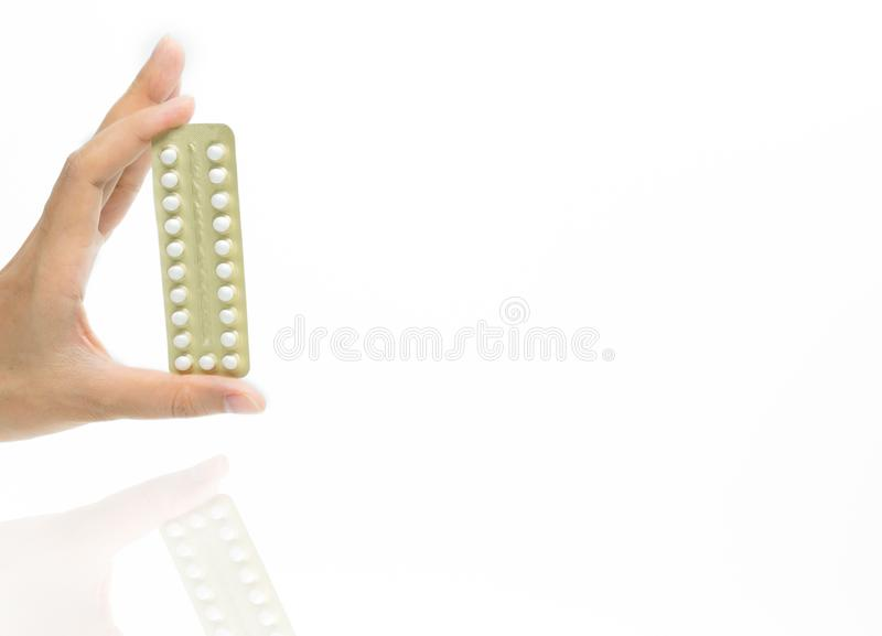 Woman hand taking birth control pills. Asian adult woman holding stock photography