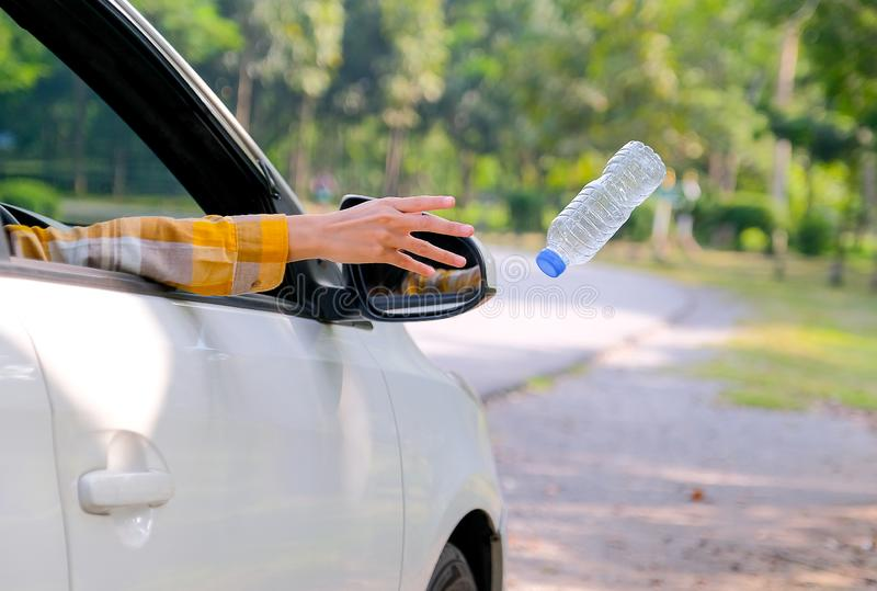 Woman hand throw clear bottle with blue cap out from car window with the concept human garbage destroy environment.  stock photo