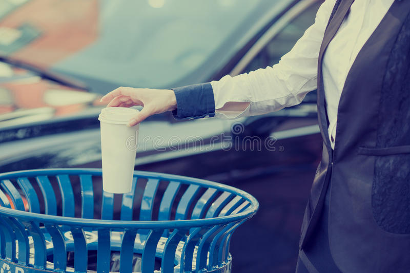 Woman hand throwing empty coffee cup in recycling bin. Closeup cropped image business woman hand throwing empty paper coffee cup in recycling bin outside city royalty free stock photos