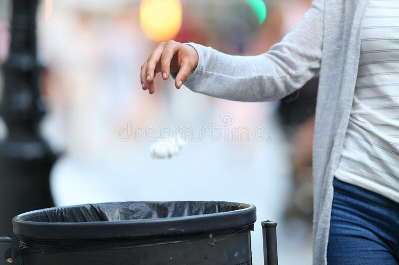 Woman hand throwing garbage to bin at evening royalty free stock photo