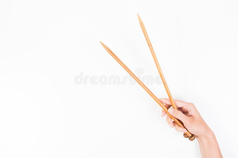 Woman hand with two wooden knitting needles over white background stock photos