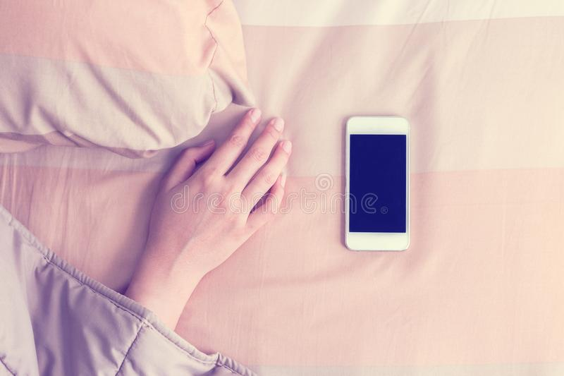 Woman hand under blanket being woken by mobile phone. royalty free stock photos
