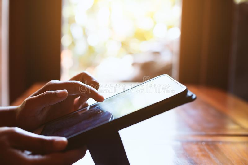 Woman hand using digital tablet in the cafe with sunlight stock images