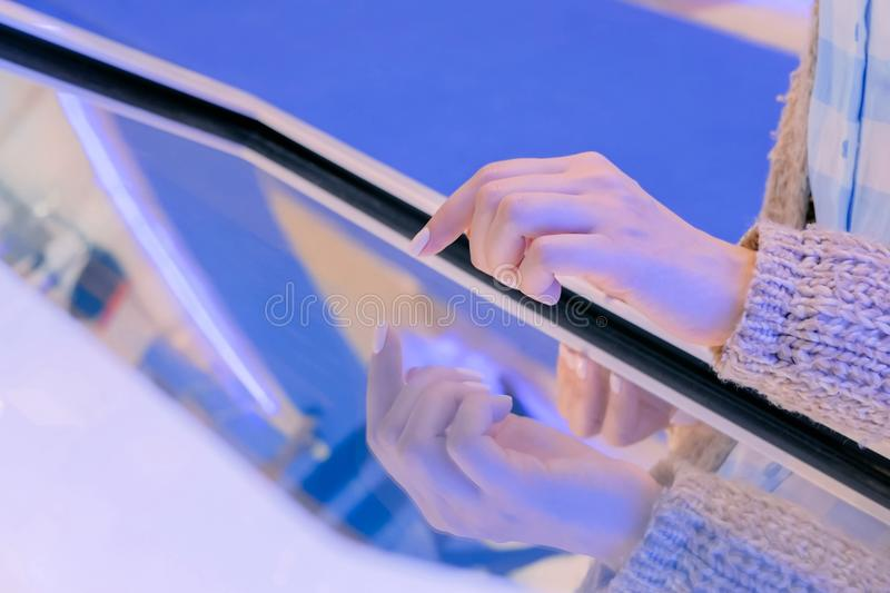 Woman using multimedia touchscreen display of interactive kiosk. Woman hand using interactive touchscreen display of white electronic multimedia terminal at stock image