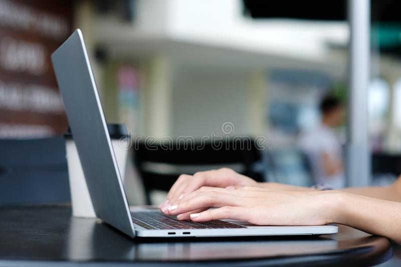 Woman hand using laptop computer at cafe outdoors background, people and technology, lifestyles stock photo