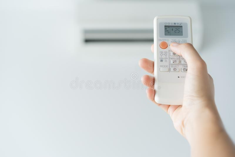 Woman hand using remote control open air conditioning 25 degrees. Open air 25 degrees, is temperature, save energy royalty free stock image