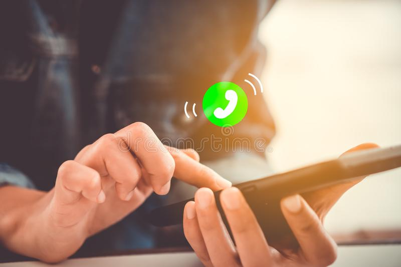 Woman hand using smartphone with incoming call icon. Woman hand using smartphone with incoming call icon in cafe shop background. Business communication social stock image