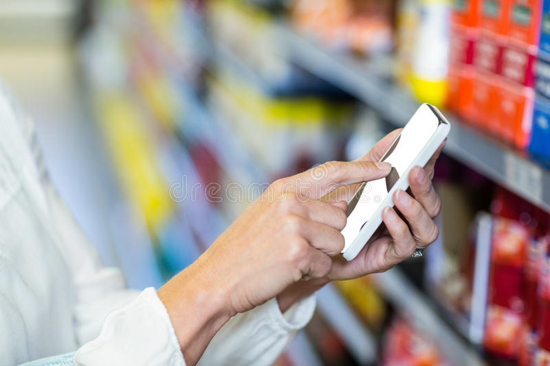 Woman hand using smartphone. In supermarket stock photos