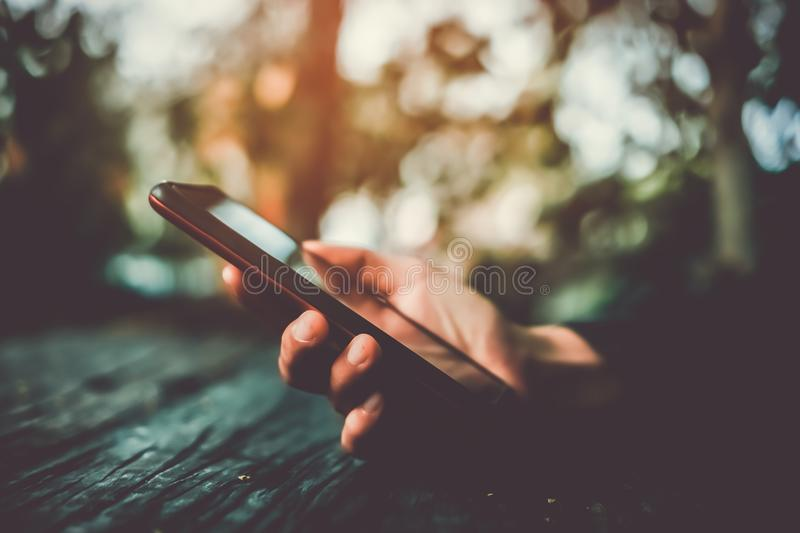 Woman hand using smartphone or tablet to do business. Woman hand using smartphone or tablet to do business, financial social network with mountain view nature stock images