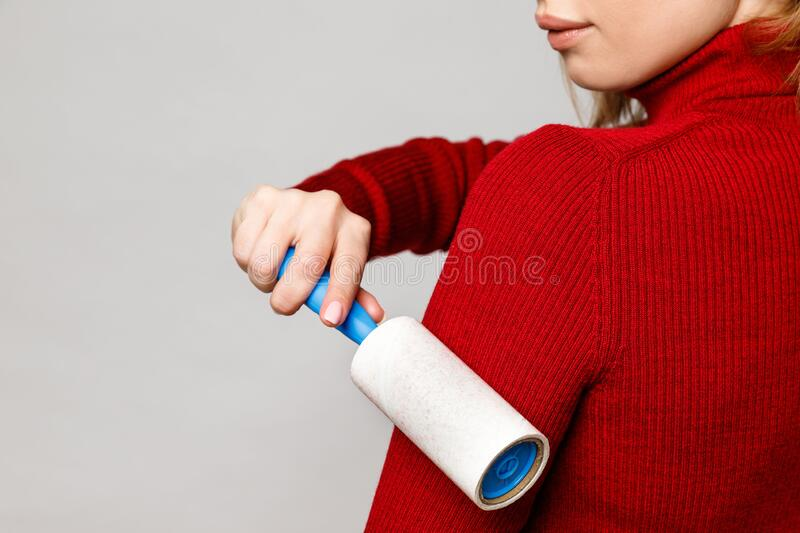 Woman hand using a sticky roller to clean fabrics - red woolen turtleneck from dust, hair, lint and fluff, front view, close up. G. Rey background stock photography