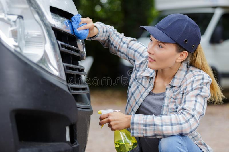 Woman hand washing car headlights royalty free stock image