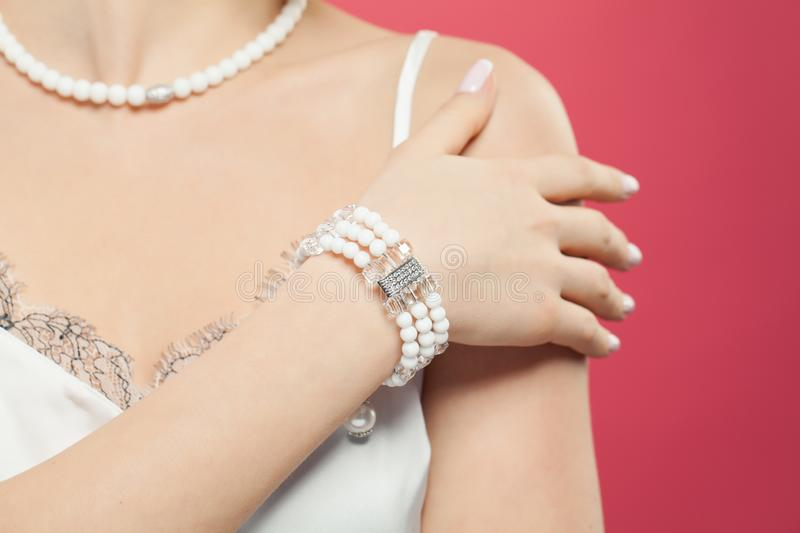 Woman hand wearing silver jewelry bracelet with pearls on pink background.  stock images