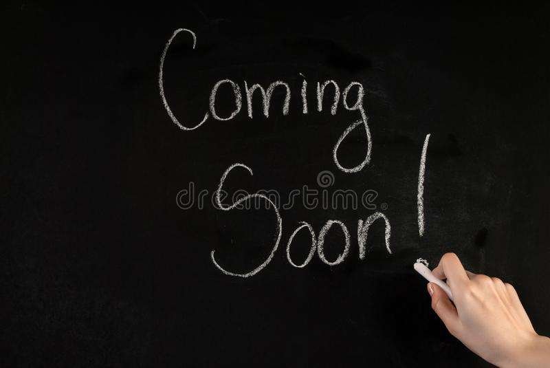 Woman hand write word Coming Soon on blackboard with white chalk. Young female hand write word Coming Soon on school blackboard with white chalk. Close up stock photos