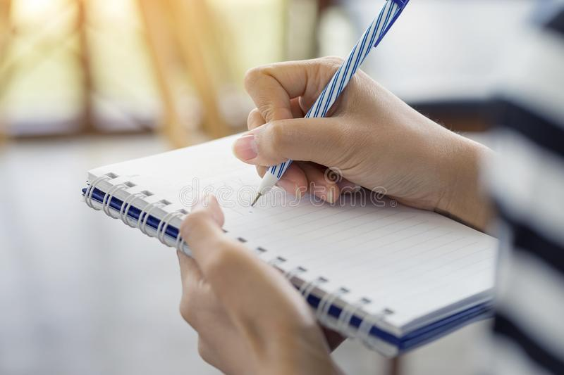 Woman hand writing check list on notebook, planning concept royalty free stock image
