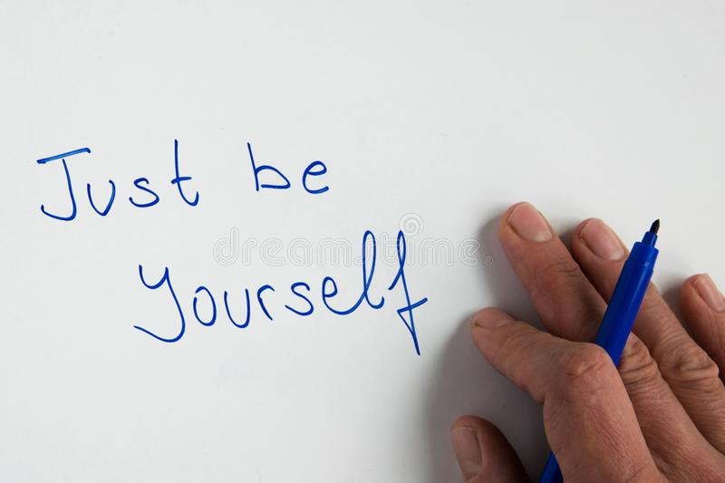 Woman hand writing the motivational phrase `Just believe` stock photos