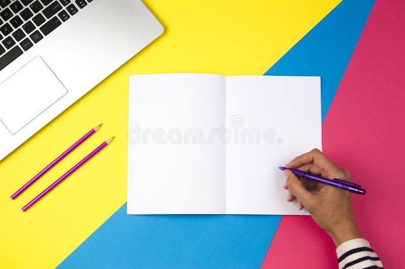 Woman hand writing in notebook on colorful background stock photo