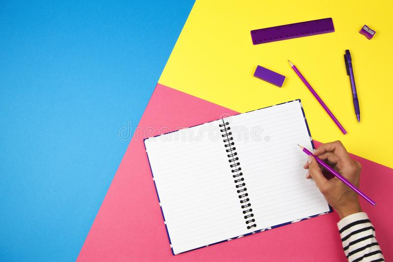 Woman hand writing in notebook on colorful background stock photos