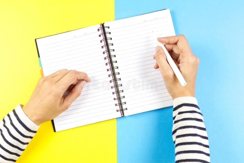 Woman hand writing in notebook over blue and yellow background. Top view stock photos