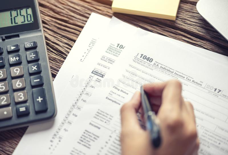 Woman hand writing U.S. tax form 1040, using calculator Individual income tax return, taxation without representation, time to. Payment concept royalty free stock photography