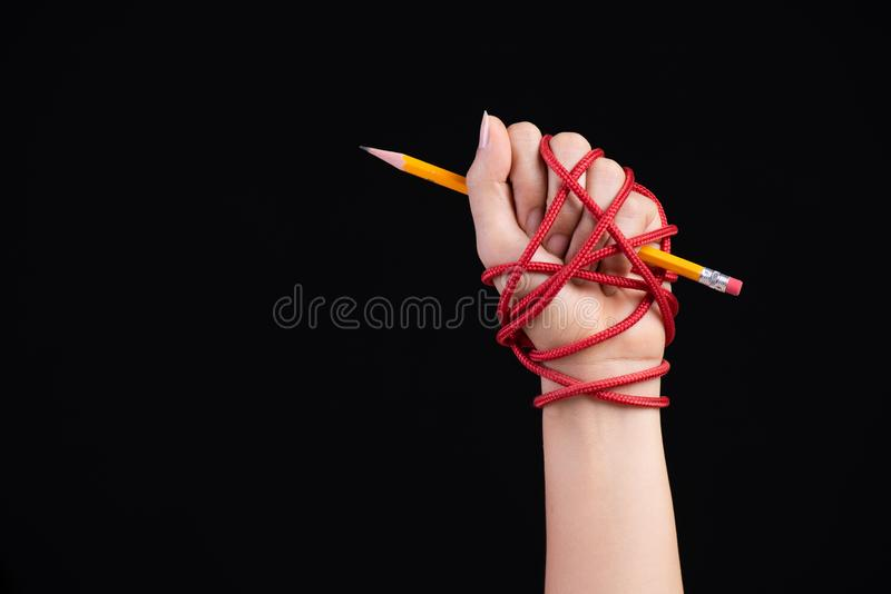 Woman hand with yellow pencil tied with red rope, depicting the idea of freedom of the press or expression on dark background. World press freedom and royalty free stock photography