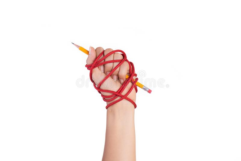 Woman hand with yellow pencil tied with red rope, depicting the idea of freedom of the press or freedom of expression on dark. Background in low key. World royalty free stock image