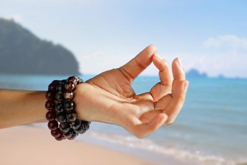 Woman hand yoga and meditation on the summer beach background royalty free stock images