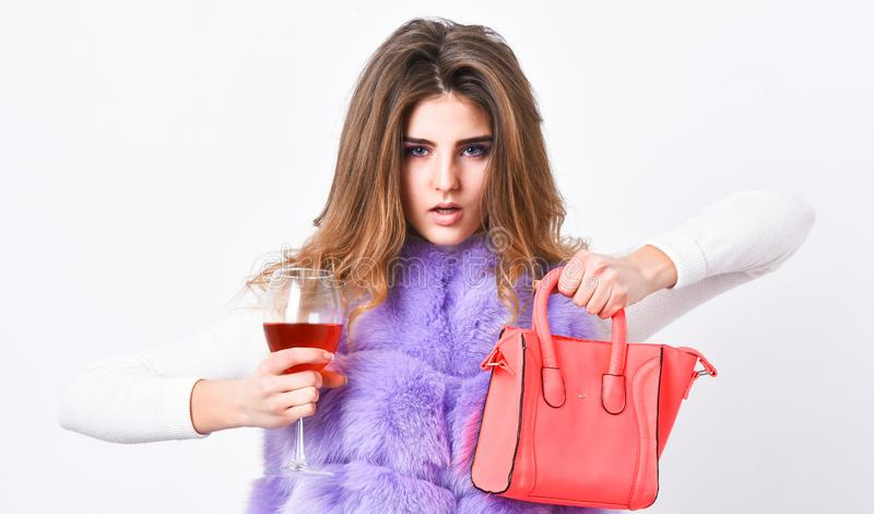 Woman with handbag hold glass of wine. Girl wear fashion fur vest while posing with bag. Luxury store concept. Elite. Fashion clothes. Lady likes shopping stock photography